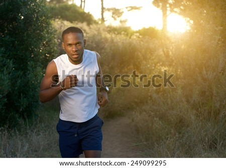 Portrait of a young african american man running outdoors - stock photo