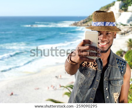 Portrait of a young african american man taking selfie at the beach - stock photo