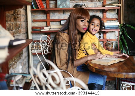 Portrait of a young African American woman and her daughter. - stock photo