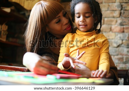 Portrait of a young African American woman and her daughter learning together.  - stock photo