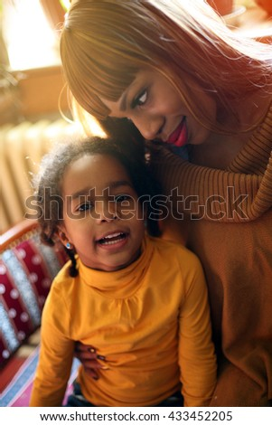 Portrait of a young African American woman and her daughter. Little girl looking at camera.  - stock photo