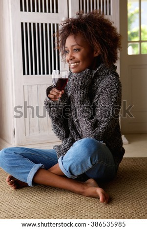 Portrait of a young african american woman enjoying a glass of wine - stock photo