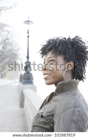 Portrait of a young african american woman in London's Thames river bank. - stock photo