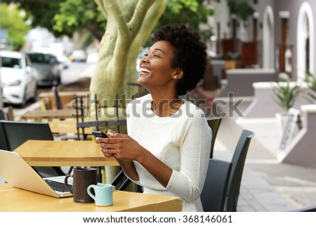 Portrait of a young african american woman sitting at a cafe and laughing with mobile phone - stock photo