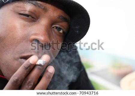 Portrait of a young African-Americans with cigarette - stock photo