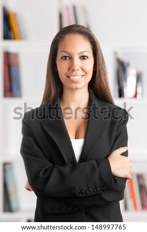 Portrait of a young african business woman with her arms crossed, smiling, in an office - stock photo