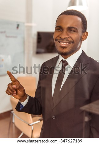 Portrait of a young African businessman during a conference in the office on the background of her colleagues