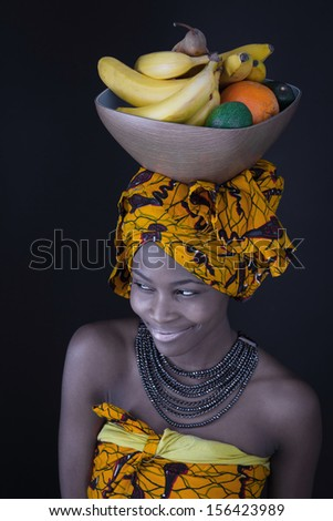 Portrait of a young African woman in traditional dress with a bowl of fruit on her head.  - stock photo