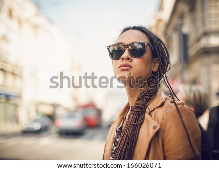 Portrait of a  young African woman wearing sunglasses outdoors. - stock photo