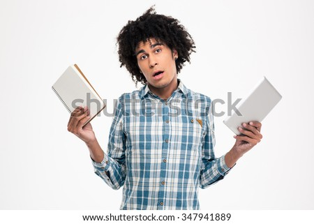 Portrait of a young afro american man choosing between paper book or tablet computer isolated on a white background - stock photo