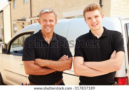 Portrait of a young and a middle aged tradesman by their van - stock photo