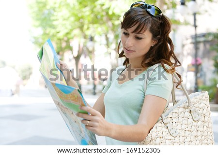 Portrait of a young and attractive tourist woman visiting a destination city during a summer holiday break and holding a map finding directions during a sunny day in a tree aligned avenue, outdoors. - stock photo