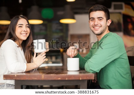 Portrait of a young and good looking Hispanic couple drinking coffee and having a good time on a date at a cafe