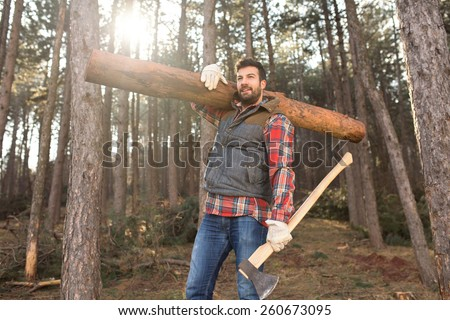 Portrait of a young and handsome lumberjack man, carrying a tree trunk on his shoulder, working hard in the forest - stock photo