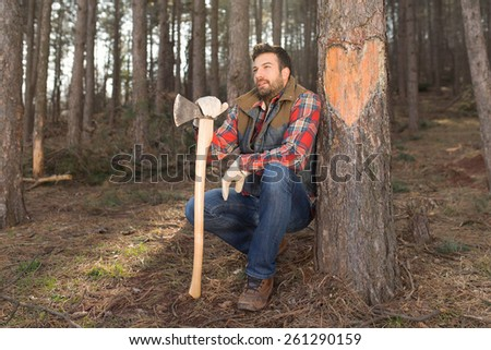 Portrait of a young and handsome lumberjack man in love, carved a heart shape in the tree with his axe - stock photo