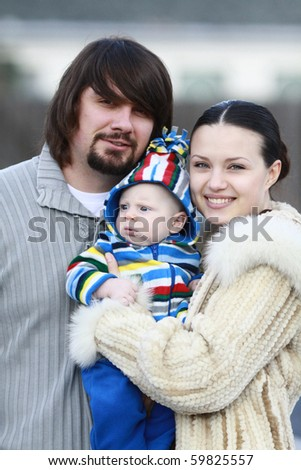 Portrait of a young and happy family outdoors. Young lovely couple outdoor holding new born baby and smiling in to the camera. blurry background. - stock photo