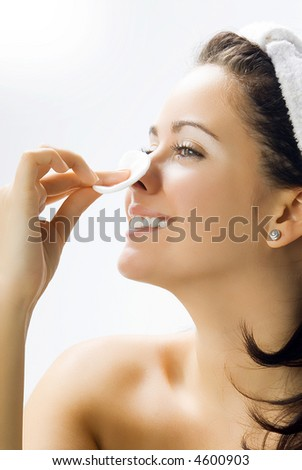 portrait of a young and pretty girl cleaning her face from make up using soft disk cleaner - stock photo