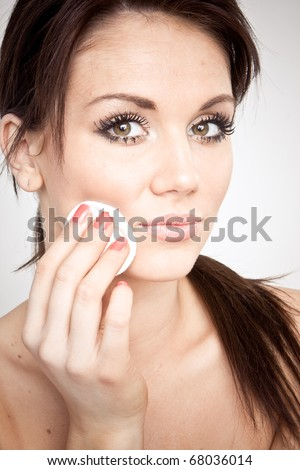 portrait of a young and pretty girl cleaning her face from make up using soft disk cleaner