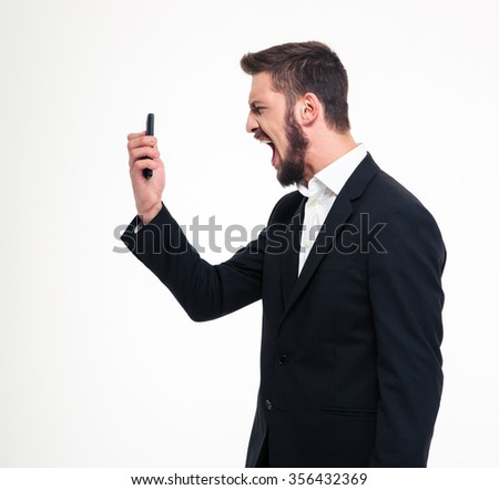 Portrait of a young angry businessman screaming on smartphone isolated on a white background - stock photo