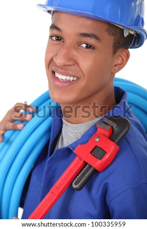 Portrait of a young apprentice with wrench - stock photo
