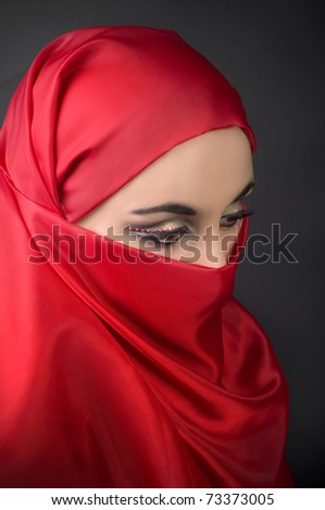 Portrait of a young   arabian girl in red veil - stock photo