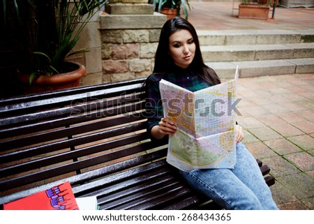 Portrait of a young asian brunette hair woman holding a map while touring abroad, attractive tourist girl reading map and resting after walk in new city while sitting on the bench - stock photo