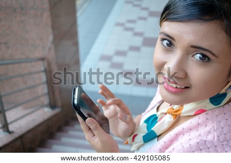Portrait of a young Asian business woman smiling and talking on smart phone, walking at an outdoor office environment