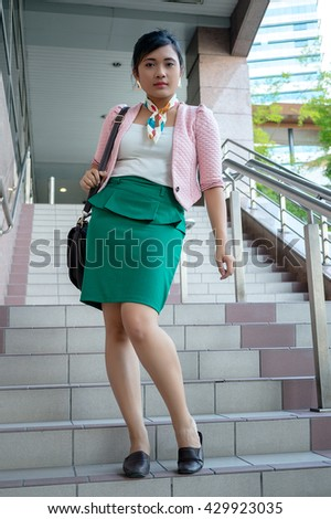Portrait of a young Asian business woman smiling, walking at an outdoor office environment