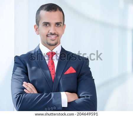 Portrait of a young Asian businessman, standing in office - stock photo