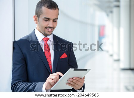 Portrait of a young Asian businessman, using tablet, standing in office - stock photo