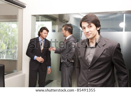 portrait of a young asian businessman with his colleagues in background - stock photo