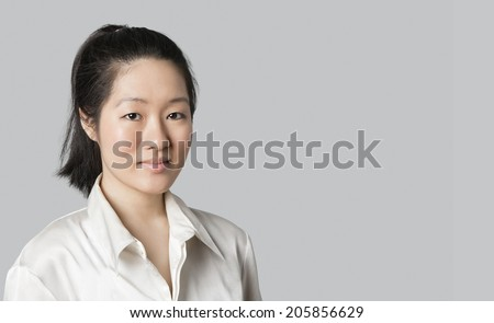 Portrait of a young Asian female doctor over gray background - stock photo