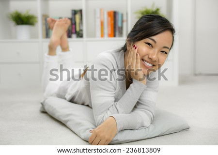 Portrait of a young Asian girl laying on the floor - stock photo