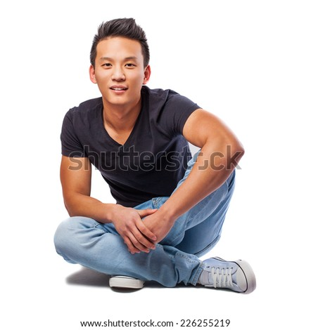 portrait of a young asian man sitting on the floor - stock photo