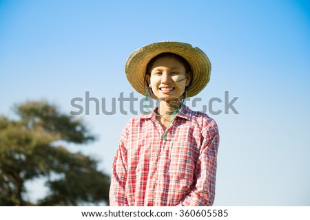 Portrait of a young Asian Myanmar farmer with thanaka powdered face who works in the field. - stock photo
