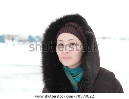 portrait of a young Asian woman in a fur coat. - stock photo