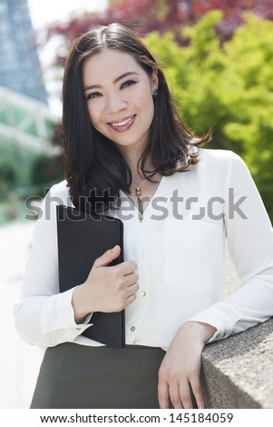 Portrait of a young Asian woman, lawyer or businesswoman smiling at a friend or colleague
