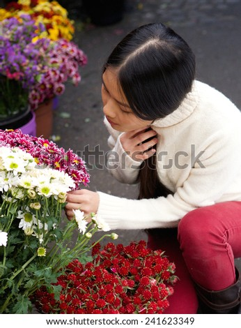 Portrait of a young asian woman looking at flowers at store