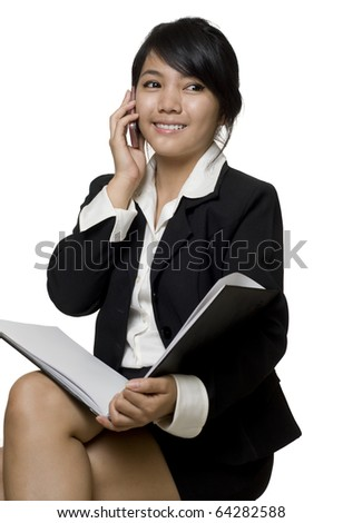 Portrait of a young attractive Asian business woman talking on the telephone - stock photo