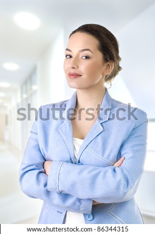 Portrait of a young attractive business woman  standing with arms crossed - stock photo