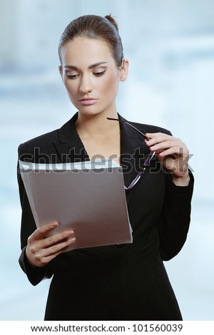 Portrait of a young attractive business woman with contract documents in her hand - stock photo
