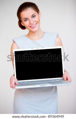 Portrait of a young attractive business woman with laptop computer - stock photo