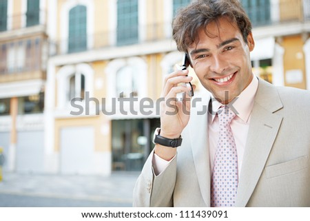 Portrait of a young attractive businessman in a European city with classic office buildings in the background, having a phone conversation. - stock photo