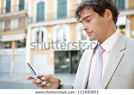 Portrait of a young attractive businessman in a European city with classic office buildings in the background, using a cell phone.