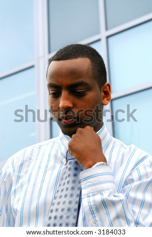 Portrait of a young attractive businessman next to a corporate building