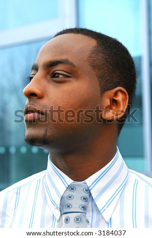 Portrait of a young attractive businessman next to a corporate building - stock photo