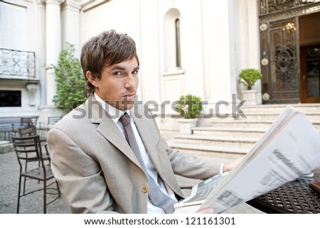 Portrait of a young attractive businessman reading the newspaper while having a coffee in a classic city coffee shop terrace with office buildings in the background. - stock photo