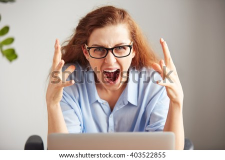 Portrait of a young attractive businesswoman with frustrated look working on laptop at  office. Outraged screaming freelance student looking at camera with desperate expression: I hate this computer  - stock photo