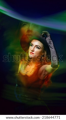 Portrait of a young attractive girl in a witch costume for Halloween shot using techniques mixed light - stock photo