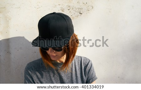 Portrait of a young attractive girl with cap.Female model wearing a black blank cap and sunglasses looking away. - stock photo